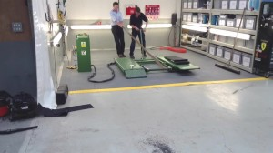 Vehicle lift installed on a MotoLock interlocking tile floor.